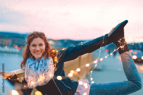 Young redhead woman posing with fairy lights outdoors teal and orange style
