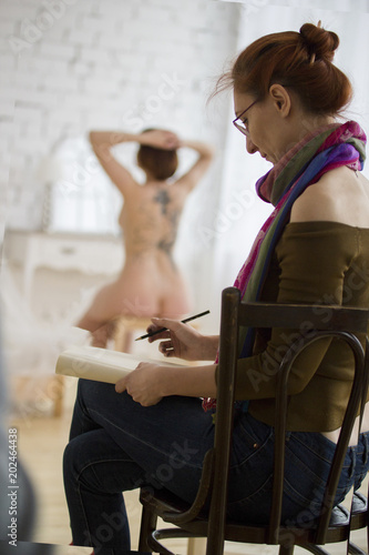 Young female artist in glasses draws nude model in light studio