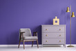 Ultra violet living room interior with retro armchair and chest of drawers next to a golden lamp. Real photo.
