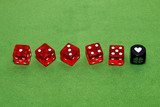 Red dices of a casino on a green table. On the last cube, the symbol