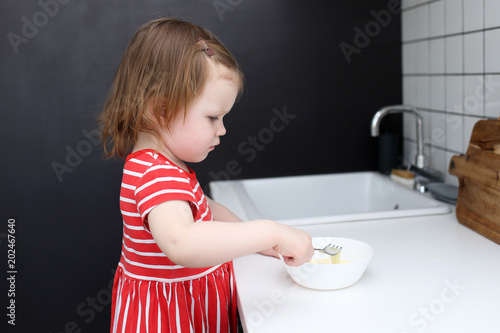 Cute 2 years girl helps cooking omelette at home kitchen