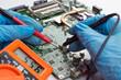Repairman disassembling laptop motherboard. Engineer fixing broken computer at work. Computer repair concept.
