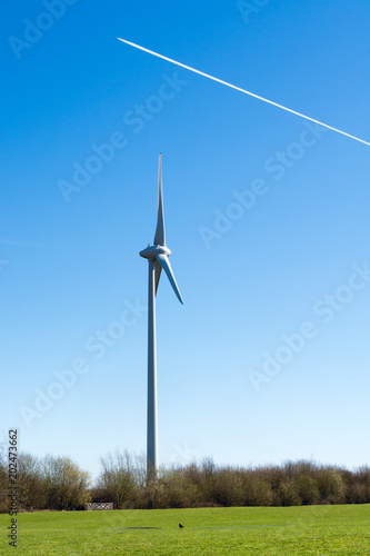 Wind turbine on sunny day with a jet trail overhead in blue sky - environmental nature background
