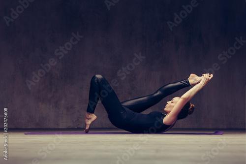 Aluminium School de yoga Young beautiful athlete is posing in studio