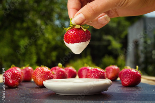 strawberries with cream on stone background, delicious first class organic fruit as a concept of summer vitamins
