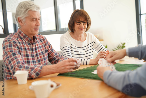 Senior friends at home playing cards