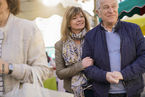 Senior couple on vacation walking in green outdoor market