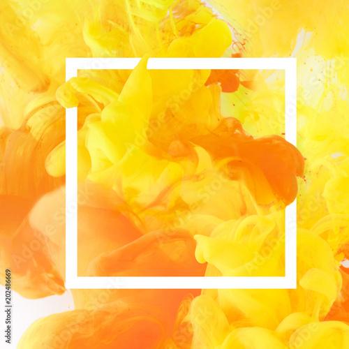 kreatywny-projekt-z-plynaca-zolta-i-pomaranczowa-farba-w-bialej-kwadratowej-ramie