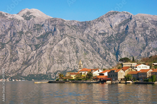 Fotobehang Donkergrijs Small Mediterranean village with stone houses with red roofs against gray mountains. Montenegro, Bay of Kotor ( Adriatic Sea ), Stoliv village