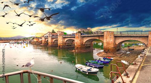 San Vicente de la Barquera.Cantabria.Paisaje idilico y pintoresco de pueblo costero.Puente de piedra sobre el mar y barcos