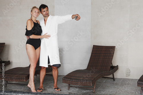 A young blonde girl in a black swimsuit and a swarthy guy in a white terry dressing gown. Make a selfie near the pool next to the brown sunbeds.