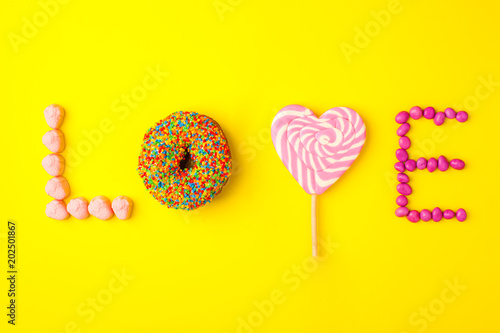 Trendy flat lay lettering. Inscription love by sweets jn yellow background