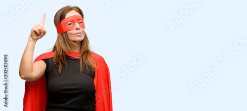 Middle age super hero woman wearing red mask and cape raising finger, the number one isolated blue background