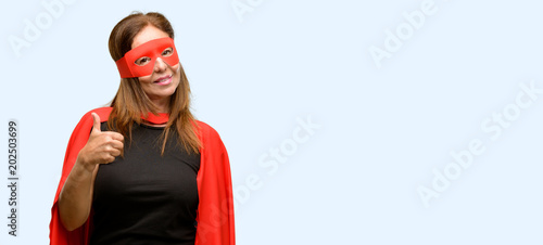 Middle age super hero woman wearing red mask and cape smiling broadly showing thumbs up gesture to camera, expression of like and approval isolated blue background