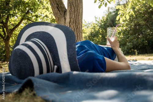 Stylish woman in a sunhat relaxing in the garden
