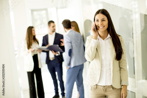 Young business woman uses the phone while other business people talking in the background