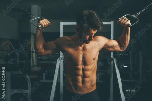 Mięśniowy mężczyzna w gym robi ćwiczeniom dla bicepsów