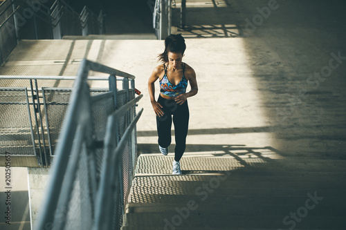 Young woman running alone up stairs © Boggy