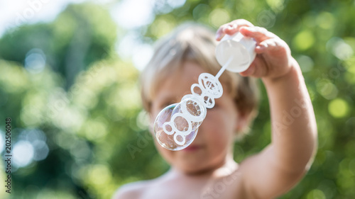 Front view of a young blond child blowing soap bubbles