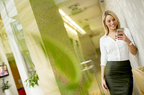 Foto Murales Portrait of a beautiful young businesswoman standing in the office using mobile phone