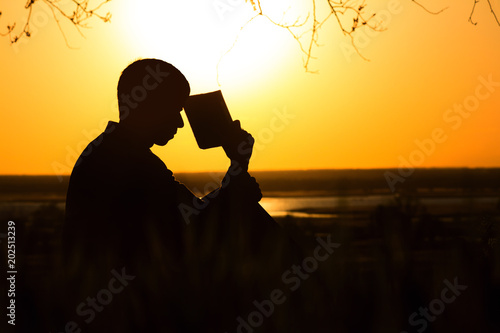 silhouette of a young man with a Bible, male praying to God in nature, the concept of religion and spirituality