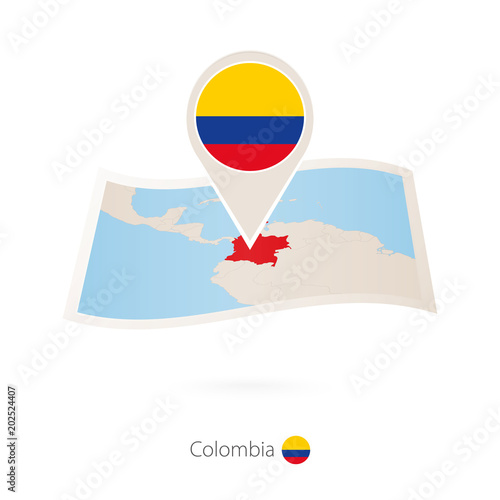 Folded paper map of Colombia with flag pin of Colombia.