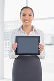 Smiling businesswoman showing tablet screen - 202535815