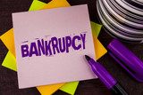 Text sign showing Bankrupcy. Conceptual photo Company under financial crisis goes bankrupt with declining sales written on Sticky note paper on wooden background Marker and Cup next to it. - 202552818