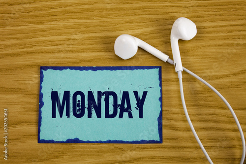 Writing note showing  Monday. Business photo showcasing First day of the week Back to work Weekend is over Wakeup Early written on Sticky Note Paper on wooden background Handsfree next to it.