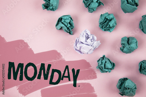 Handwriting text Monday. Concept meaning First day of the week Back to work Weekend is over Wakeup Early written on Painted Pink background Crumpled Paper Balls next to it.