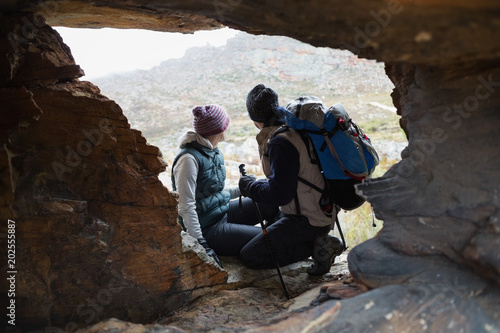 Plexiglas Chocoladebruin Couple seen through rock cave while on a hike