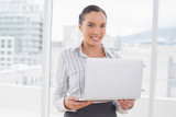 Standing businesswoman using a laptop - 202563690