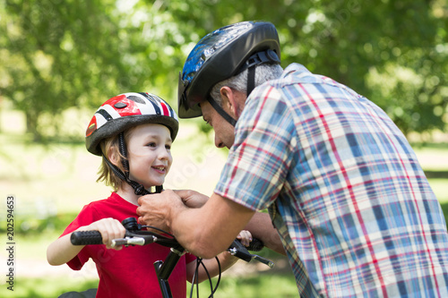 Fototapeta Father attaching his sons cycling helmet