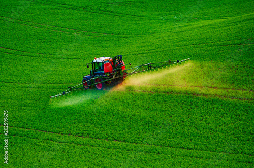 Fotobehang Groene Farm machinery spraying insecticide to the green field, agricultural natural seasonal spring background