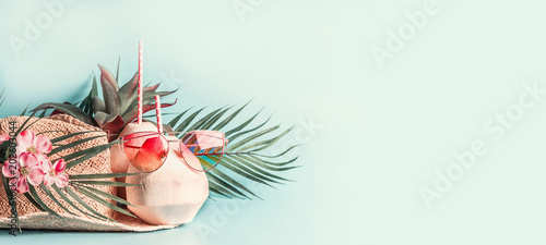 Summer holiday . Beach accessories : straw hat with palm leaves and flowers, pink sun glasses and coconut cocktail on blue turquoise background, front view. Tropical vacation travel concept. Banner