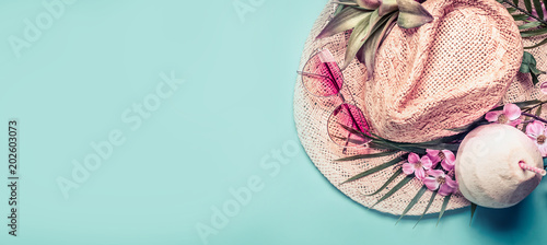 Summer holiday banner.  Beach accessories : straw hat, palm leaves, pink sun glasses, flowers and coconut cocktail on blue turquoise background, top view. Tropical vacation travel concept - 202603073