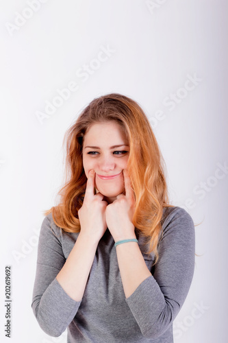 beautiful young woman forcing a smile, holding her fingers near lips