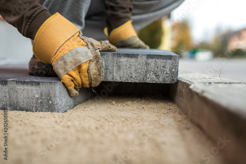Workman laying exterior paving stones