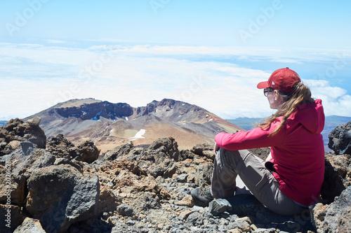 Canvas Canarische Eilanden girl in red jacket looking at rocky desert landscape on top of teide volcano tenerife
