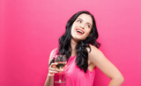 Young woman drinking wine on a solid pink background - 202665858