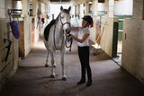 Teenage girl standing with horse - 202668665
