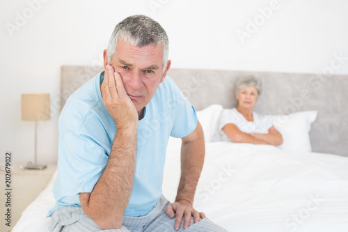 Sad senior man with woman in bed