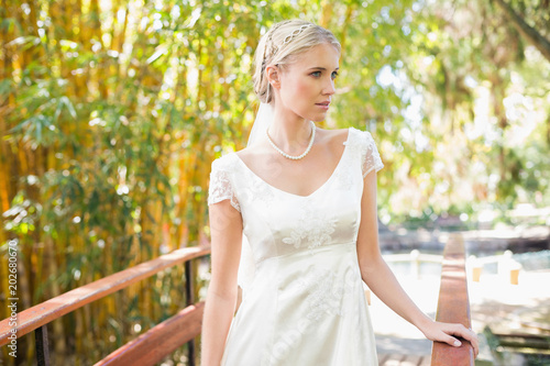 Smiling blonde bride in pearl necklace standing on a bridge © WavebreakmediaMicro