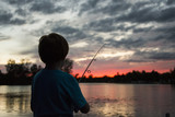 Young boy fishing on a lake with a beautiful sunset