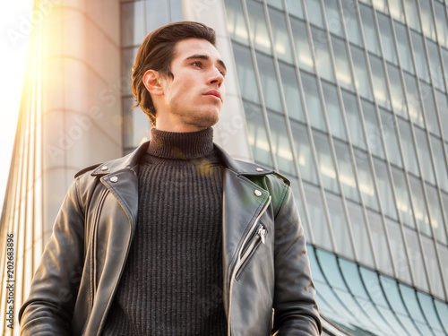 One handsome young man in urban setting in modern city, standing, wearing black leather jacket and jeans