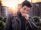 One handsome young man in urban setting in modern city, standing, wearing black leather jacket and jeans, looking at camera, at sunset