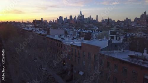 sunset flying backwards away from Manhattan skyline revealing solar panels on Brooklyn roof
