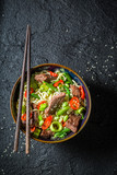 Hot asian noodle with beef and vegetables on black table - 202685688