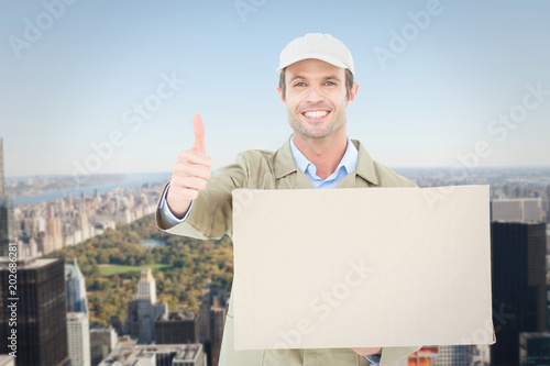 Happy delivery man gesturing thumbs up while carrying cardboard box against new york