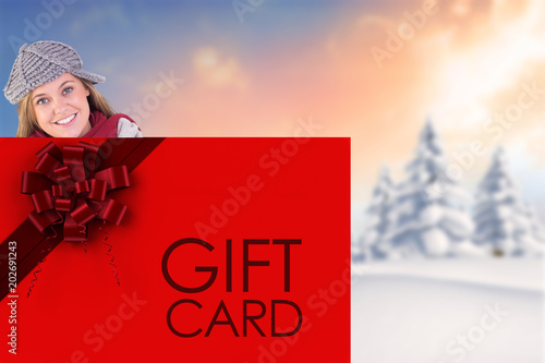 Fotobehang Rood traf. Happy blonde in winter clothes showing card against snowy landscape with fir trees